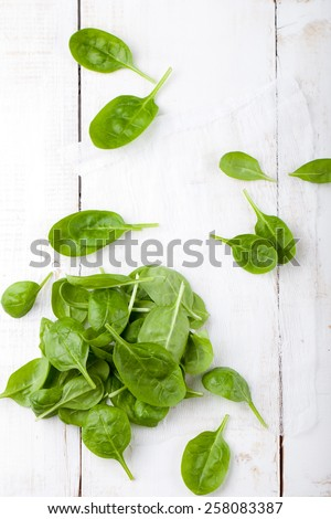 Spinach baby leaves on a white wooden background. copy space - stock photo