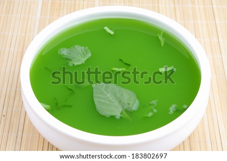 Spinach cream soup with fresh spinach leaf on top. - stock photo