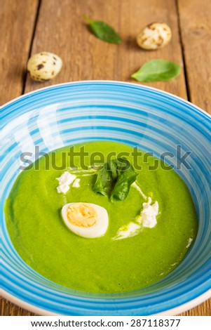 Spinach cream soup with leaf, egg and sour cream on rustic wooden table - stock photo