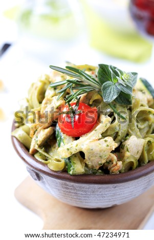 Spinach fettuccine with chicken, basil pesto and cream - stock photo