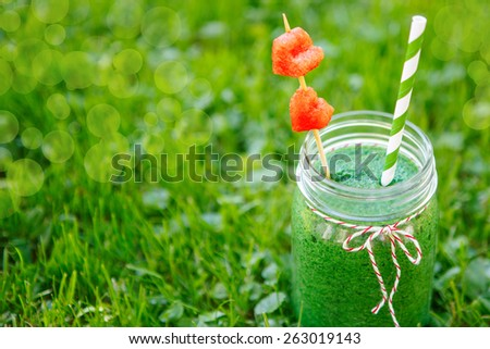 Spinach green smoothie as healthy summer drink. Bio organic and vegan beverage. With red watermelon hearts on skewer. - stock photo
