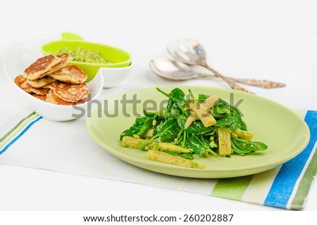 spinach salad with avocado and corn; pancakes with corn - stock photo