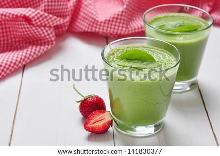 Spinach smoothies in glass served with strawberry on a wooden background - stock photo
