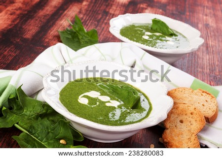 Spinach soup with spinach leaves and fresh bread on brown wooden background. Culinary spinach soup eating.  - stock photo