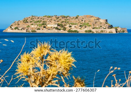 Spinalonga Island, Crete, Greece. Plants in the foreground are blurred - stock photo