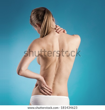 Spine therapy. Close-up of woman with naked back suffering from backache over blue background. - stock photo