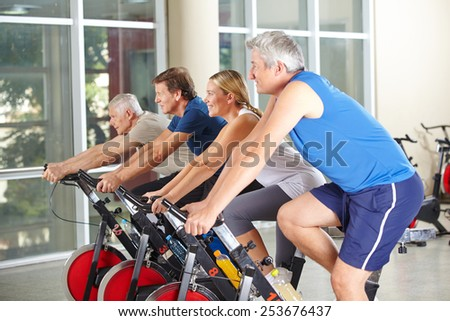 Spinning class with four happy senior people in a gym - stock photo
