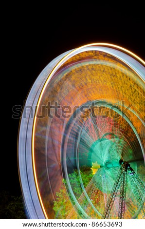 Spinning ferris wheel at fair at night - stock photo
