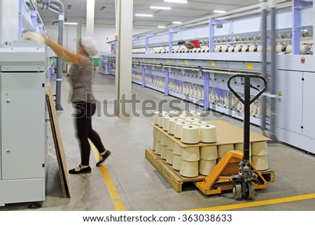 Spinning machinery parts and workers in the factory, closeup of photo - stock photo