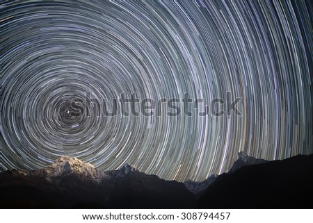 Spinning Universe. Star trails over the mountains. Annapurna South (7,219 m), Hiunchuli (6,441 m),  Gangapurna (7,454 m) and Annapurna III (7.555 m), and unclimbed mountain Machhapuchhre (6,997 m). - stock photo