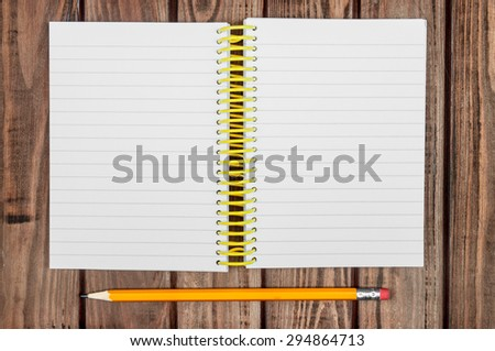 Spiral bound notebook with pen on the dark wooden background.  - stock photo