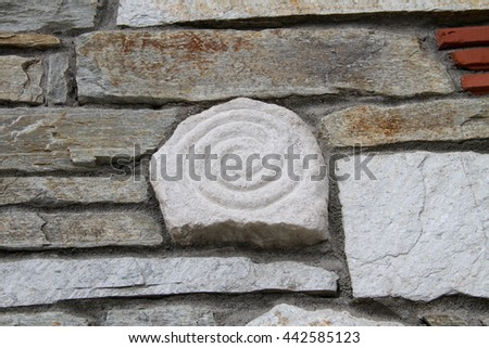 Spiral carved in white stone as a detail on a stone wall. - stock photo