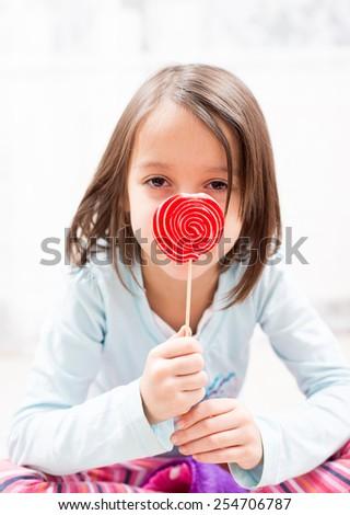 spiral colored sugar lollipop, in girl hand - stock photo