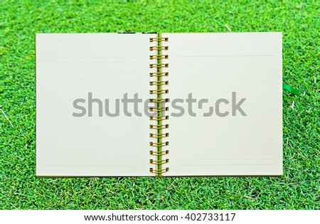 Spiral leather notebook on grass - stock photo