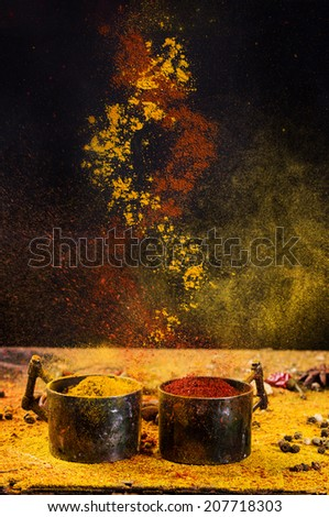 Spiral mixing of  spices red pepper and turmeric from vintage metal cups over black background. Concept. - stock photo