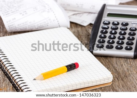 Spiral notebook, pencil,calculator and grocery shopping receipts - stock photo