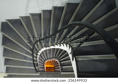 Spiral staircase with warm orange light at the end - stock photo