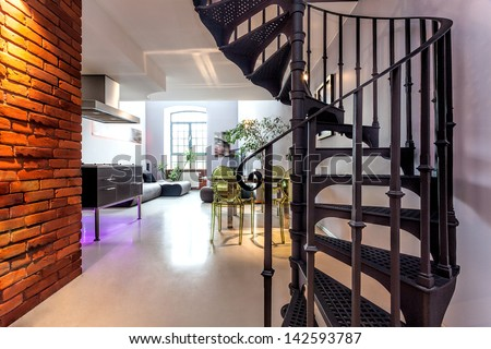 Spiral stairs and living room in modern loft - stock photo