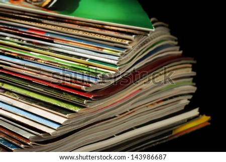 Spiraled stack of colorful magazines and mail order catalogs (with slightly worn edges) on black background with copy space.  Macro with shallow dof. - stock photo