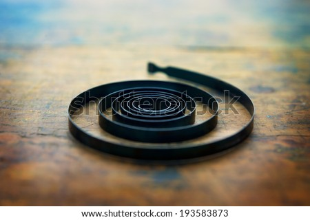 Spirally expanding. Clock spring, power spring or power coil, on a old work desk - stock photo