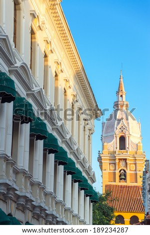 Spire of the cathedral in Cartagena, Colombia with a white historic colonial building also visible - stock photo