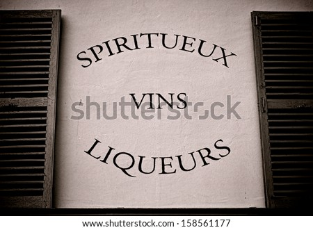 Spirit wine and liquor store vintage advertising sign in French painted on an old wall between two shutters above an alcohol and beverage traditional shop in a small town in France - stock photo