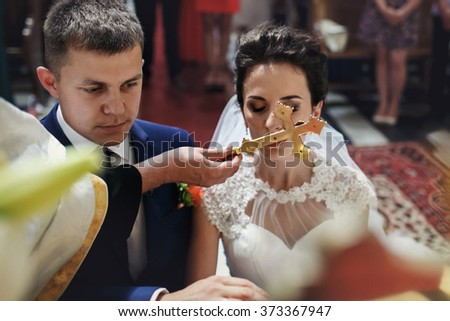 Spiritual beautiful bride and groom taking vows in churchm kissing crucifix - stock photo