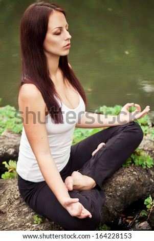 Spiritual fit woman sitting in lotus pose on a river stone - stock photo
