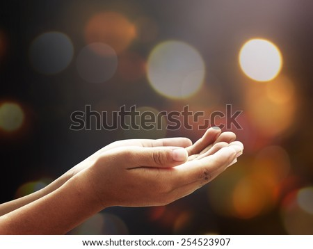 Spiritual hands or human poverty over blurred bokeh light night background. Hands of pay obeisance. Light of the world, Person hands begging for food or help concept. - stock photo