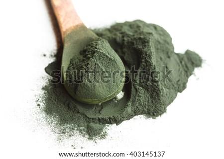 spirulina algae powder on wooden spoon isolated on white - stock photo