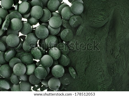 Spirulina powder and tablets algae nutritional supplement heap surface close up top view,  background  - stock photo
