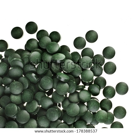 Spirulina tablets  algae nutritional supplement heap surface close up top view, isolated on white background  - stock photo