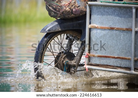 Splash by a motorcycle as it goes through flood water - stock photo