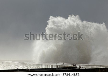 Splash from a big wave against a pier from the north of Portugal against an overcast sky before rain - stock photo