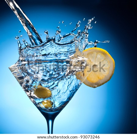 Splash from pouring martini into the glass. Object on a blue background. - stock photo
