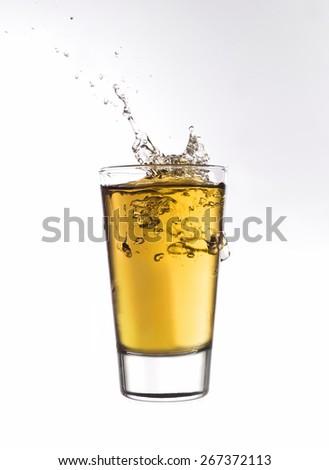 Splash in a glass of orange lemonade isolated on white background - stock photo
