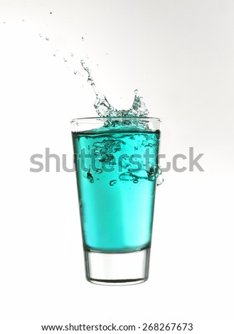 Splash in a glass of turquoise lemonade isolated on white background - stock photo