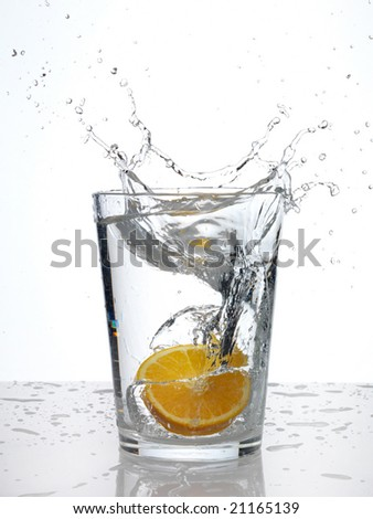 Splash in a glass on white. Slice of orange. - stock photo
