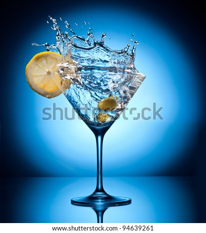 Splash martini from flying olives. Object on a blue background. - stock photo