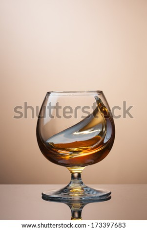 Splash of cognac in glass on brown background - stock photo
