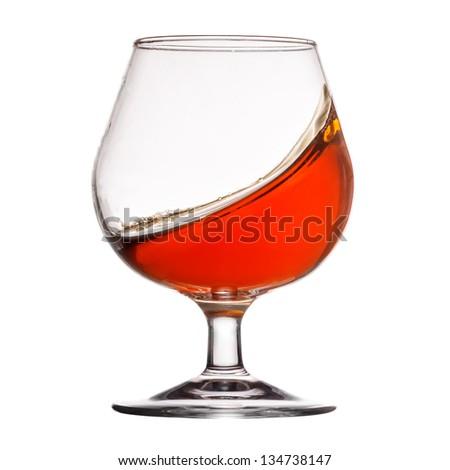 Splash of cognac in glass on white background - stock photo