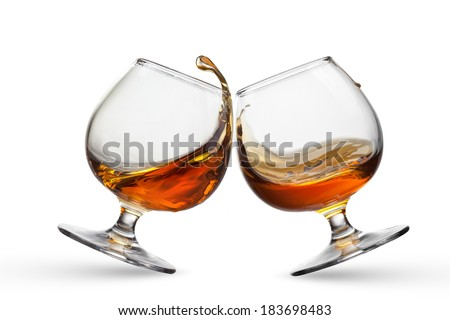 Splash of cognac in two glasses isolated on white background - stock photo
