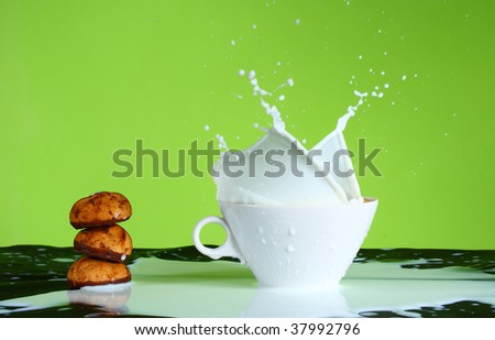 splash of milk in a mug on a green background - stock photo