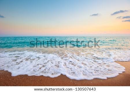 Splash of sea foam on a sandy beach - stock photo
