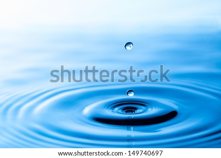 Splash of water crown on blue surface - stock photo