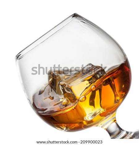 Splash of whiskey with ice in glass isolated on white background.  - stock photo