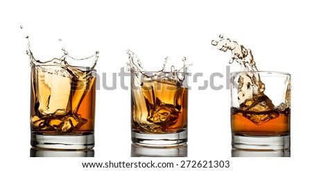 splash of whiskey with ice isolated on white  - stock photo