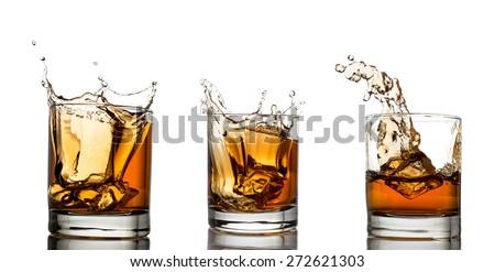 splash of whiskey with ice osolated on white  - stock photo