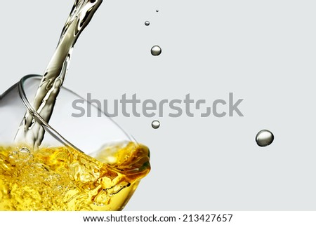 Splashing beverage poured inside a glass.   - stock photo