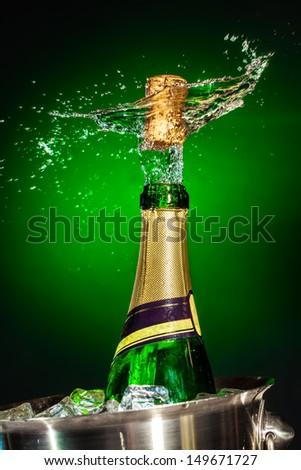 Splashing champagne on a green background - stock photo
